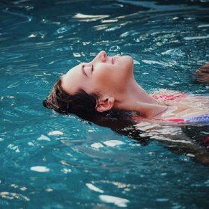 Frau liegt lächelnd im Wasser